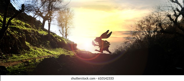White rabbit holding pocket-watch running across woody horizon