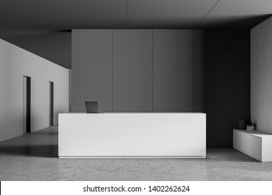 White reception desk with laptop computer on it standing in modern office lobby with gray and white walls and concrete floor. 3d rendering