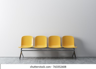 White room interior with a concrete floor and a row of yellow chairs standing near the wall. Concept of a waiting room. 3d rendering mock up