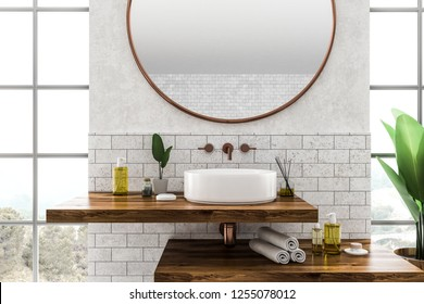 White round bathroom sink standing on wooden shelf with round mirror above it in room with white and brick walls and large windows. 3d rendering