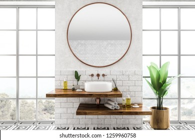 White round bathroom sink standing on wooden shelf with round mirror above it in room with white and brick walls, large windows and tiled floor. 3d rendering