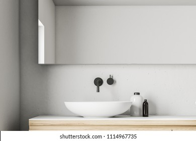 White saucer like bathroom sink standing on a wooden countertop of a Scandinavian style bathroom interior with a large horizontal mirror hanging above it. 3d rendering