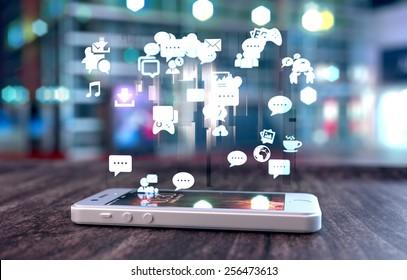 Telefone inteligente branco em uma mesa de madeira emitindo imagem holográfica de ícones relacionados às mídias sociais. Fundo turva da cidade.