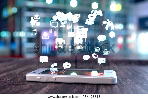 White smart phone on a wooden table emitting holographic image of social media related icons. Blurred city background.