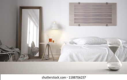 White table or shelf with crystal hourglass measuring the passing time over modern bedroom with double bed, architecture interior design, copy space background, 3d illustration