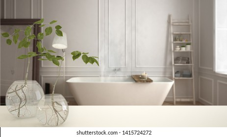White table top or shelf with glass vase with hydroponic plant, ornament, root of plant in water, branch in vase, house plant, modern blurred bathroom background, interior design, 3d illustration