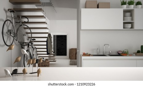 White table top or shelf with minimalistic bird ornament, birdie knick - knack over blurred kitchen and living room with stairs and bike, modern interior design, 3d illustration