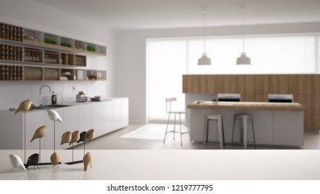 White table top or shelf with minimalistic bird ornament, birdie knick - knack over blurred minimalistic kitchen with island and stools, modern interior design, 3d illustration