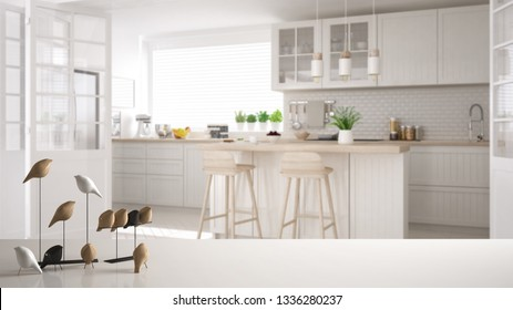 White table top or shelf with minimalistic bird ornament, birdie knick - knack over blurred contemporary white scandinavian kitchen with island and stools, modern interior design, 3d illustration