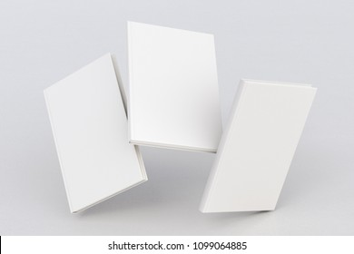 White vertical three blank book cover flying over white background with clipping path around each book cover. 3d illustration