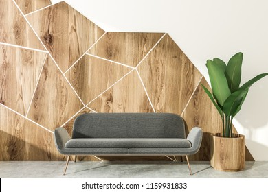 White and wooden geometric wall pattern living room interior with a concrete floor, a gray sofa standing next to a coffee table and plant in pot. 3d rendering mock up