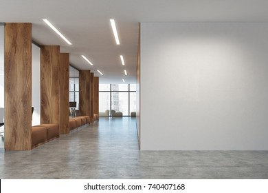 White and wooden open space office with a blank white wall, a row of soft comfortable sofas and computer desks in the background. 3d rendering mock up