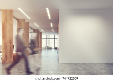 White and wooden open space office with a blank white wall, a row of soft comfortable sofas and computer desks in the background. People 3d rendering mock up toned image