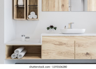 White and wooden wall bathroom interior with a concrete floor, a sink with a long horizontal mirror and shelves with rolled towels. 3d rendering copy space