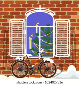 Window of an old house and a bicycle under a layer of snow