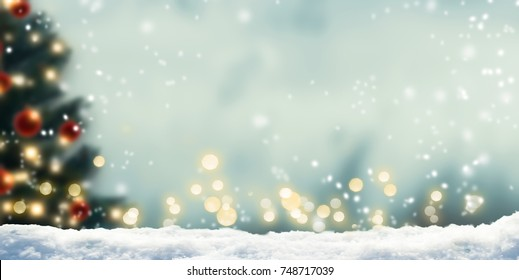 winter background with blurred xmas tree and bokeh lights, beautiful christmas lights in abstract snow landscape with advertising space