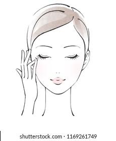 Woman applying cream around her eyes