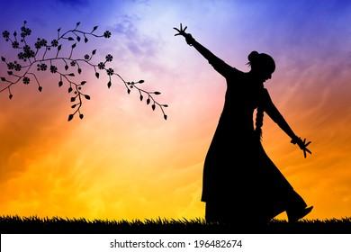 Woman dancing indian dance at sunset