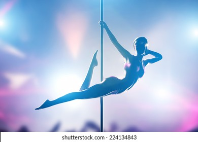 Woman performs sensual, passionate pole dance in night club. Sexy body silhouette, professional, sexual pose.