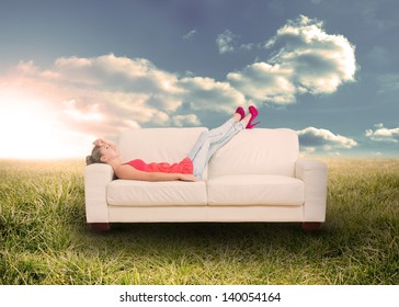 Woman relaxing on  the couch in sunny field in the countryside