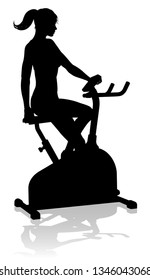 A woman in silhouette using a stationary exercise spin bike piece of gym equipment fitness machine