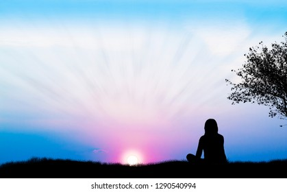 woman watching the sunset in the field