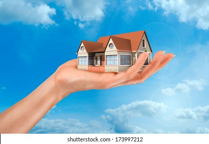 a woman's hand holding a house on sky background