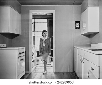 Women enters a modern 1940s kitchen with white enameled metal cabinets. The housing was built by the government for workers on TVA and other Defense projects in World War II. Dec 1941.