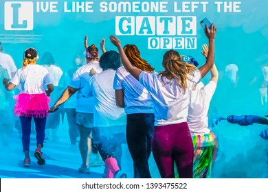 Women run in a holi color run race with arms raised with blue powder swirling around them- LIVE LIKE SOMEONE LEFT THE GATE OPEN