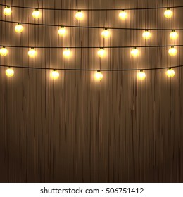 Wooden background with lighting garland festive decoration, with strings of round lamps.