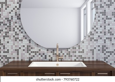 Wooden bathroom sink near a gray tiled wall with a large round mirror hanging above it. 3d rendering