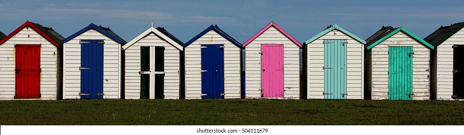 Wooden Holiday Beach Huts illustration with red, blue,  green black pink doors.