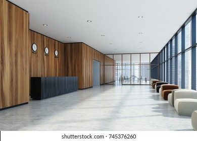 Wooden office lobby with a concrete floor, panoramic windows, a black wooden reception desk and a row of armchairs. 3d rendering mock up