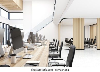 Wooden open space office interior with panoramic windows, two rows of white computer tables with monitors on them, black chairs and stairs in the corner. 3d rendering mock up