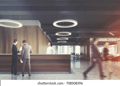 Wooden reception desk is standing in a modern office with a concrete floor, light wooden walls, round ceiling lamps and armchairs. People. 3d rendering mock up toned image