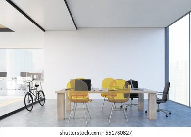Wooden table with yellow transparent chairs and a glass wall. Panoramic window. Large open office space is to the left of it. 3d rendering.