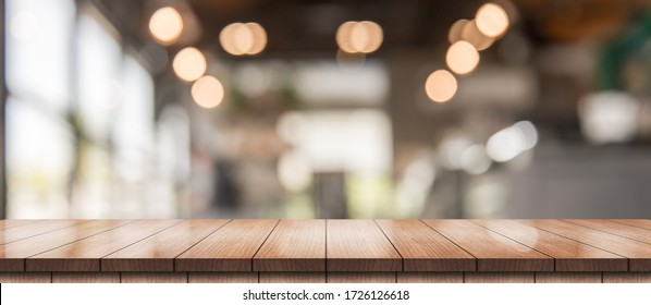 Wooden top table with bokeh light effect and blur restaurant on background, blur background