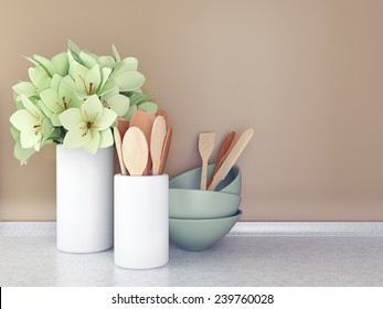 Wooden utensils and flowers on the white marble worktop in front of brown wall.