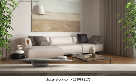 Wooden vintage table or shelf with stone balance, over blurred classic living room with sofa and floor lamp, feng shui, zen concept architecture interior design, 3d illustration