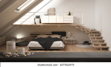Wooden vintage table top or shelf with candles and pebbles, zen mood, over blurred loft mezzanine scandinavian minimalist bedroom, white architecture interior design, 3d illustration