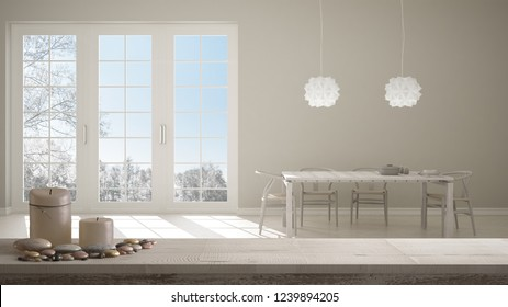 Wooden vintage table top or shelf with candles and pebbles, zen mood, over blurred classic white kitchen with wooden details, dining table laid for two, modern interior design, 3d illustration