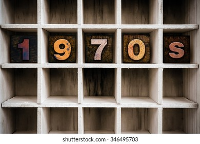 "The word ""1970s"" written in vintage ink stained wooden letterpress type in a partitioned printer's drawer."