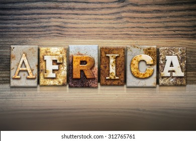 """The word """"AFRICA"""" written in rusty metal letterpress type sitting on a wooden ledge background."""