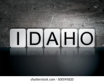 """The word """"Idaho"""" written in white tiles against a dark vintage grunge background."""