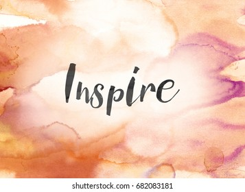 The word Inspire concept and theme written in black ink on a colorful painted watercolor background.