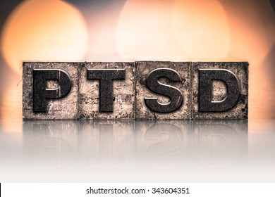 "The word ""PTSD"" written in vintage ink stained letterpress type."
