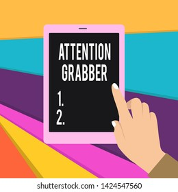 Word writing text Attention Grabber. Business concept for Deanalysisding notice mainly by being prominent or outlandish Female Hand with White Polished Nails Pointing Finger Tablet Screen Off.