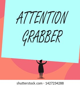 Word writing text Attention Grabber. Business concept for Deanalysisding notice mainly by being prominent or outlandish Back view standing short hair woman dress hands up holding blank rectangle.