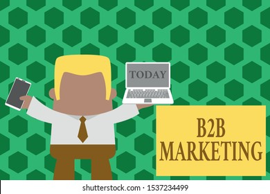 Word writing text B2B Marketing. Business concept for Partnership Companies Supply Chain Merger Leads Resell Standing professional man tie holding left open laptop right mobile phone.