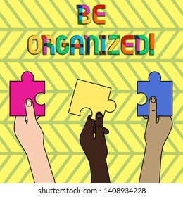 Word writing text Be Organized. Business concept for Being able to plan things carefully and keep things tidy Three Colored Empty Jigsaw Puzzle Pieces Held in Different People Hands.